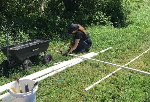 Undergraduate intern Sara Mecca saws a PVC pipe for the sensor installation.
