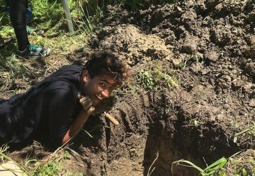 Undergraduate intern Kunal Palawat poses by a soil pit.